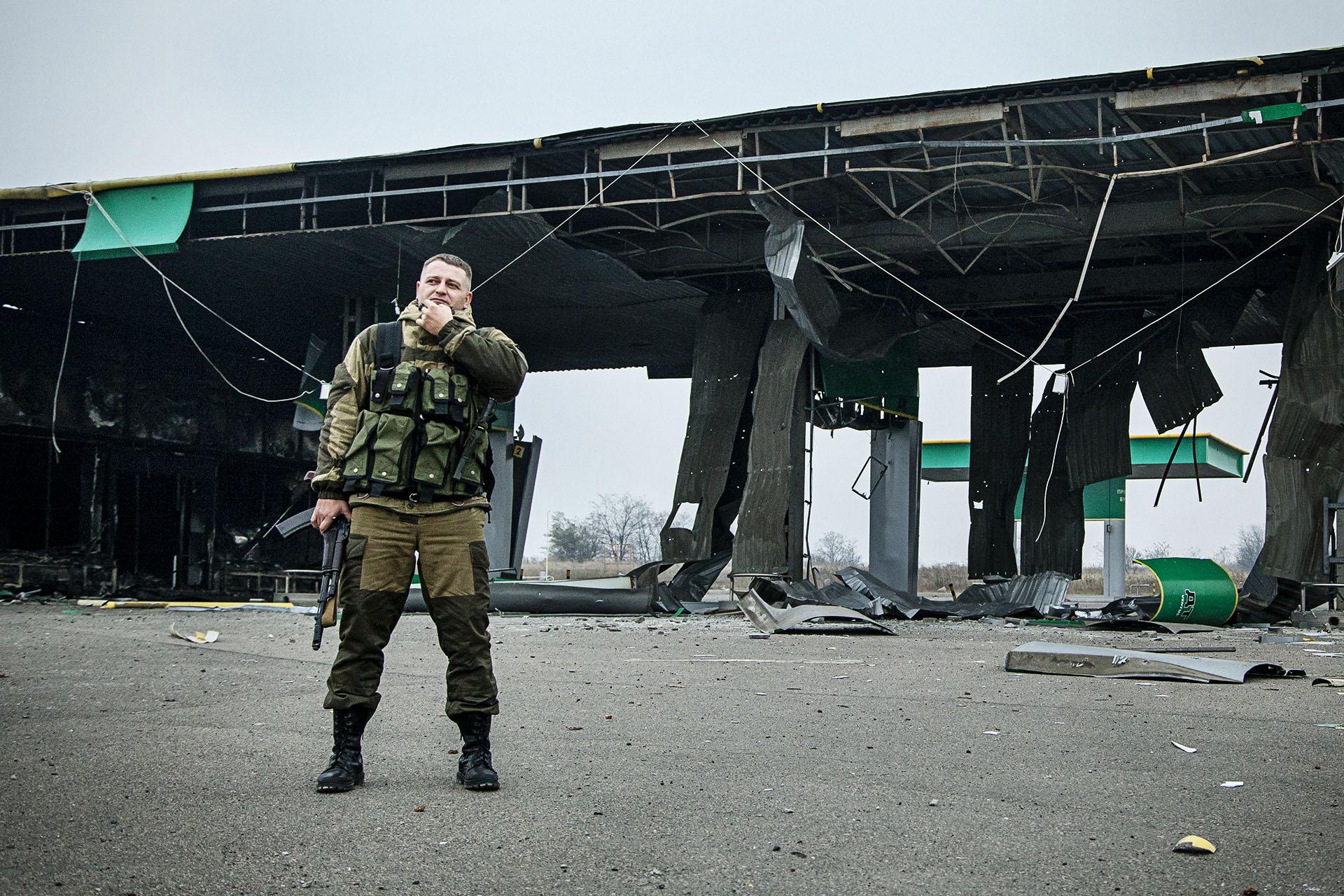 """""""Krest"""", uno de los comandantes del batallón """"Vostok"""", ante una gasolinera destruída durante los conflictos con las tropas ucranianas"""