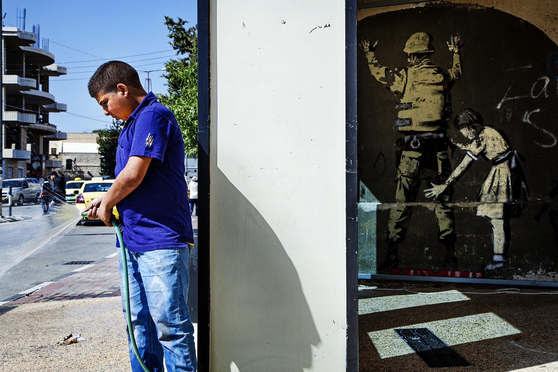 Un niño palestino limpia la calle cerca de un famoso mural del artista Banksy en Bethlehem.