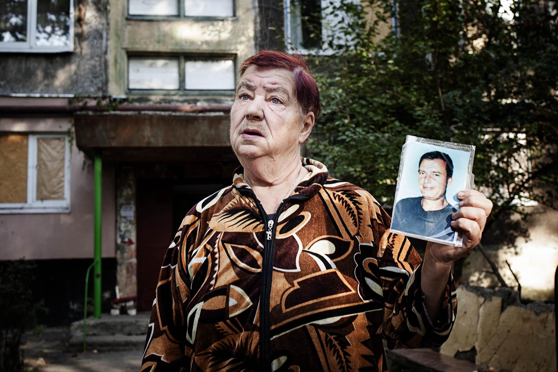 Una mujer muestra una foto de su hijo, muerto durante los bombardeos del ejército ucraniano que arrasaron el barrio de Oktobersky / (Donetsk).