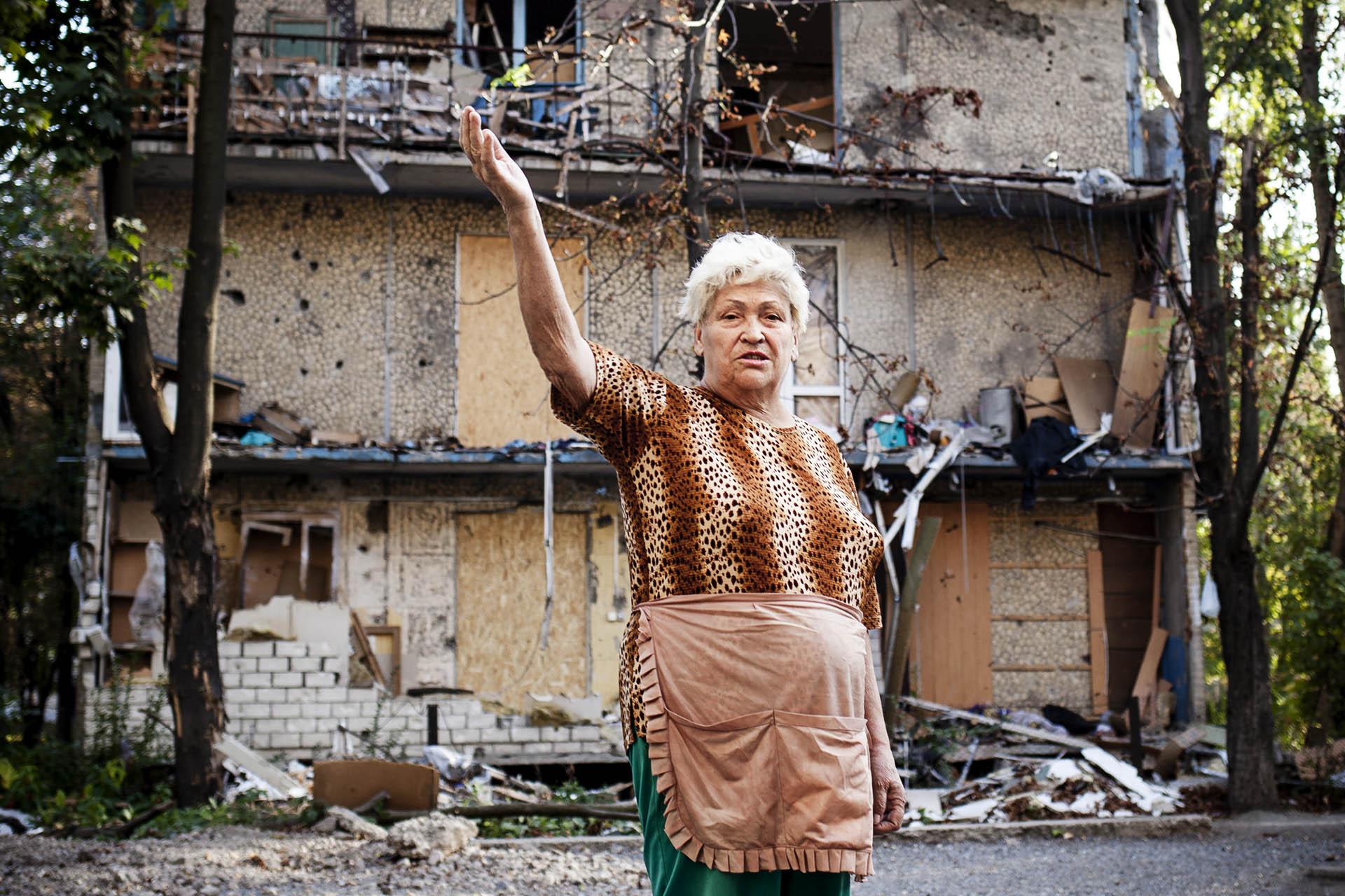 Una mujer muestra los destrozos causados en su barrio por la artillería ucraniana / (Donetsk).