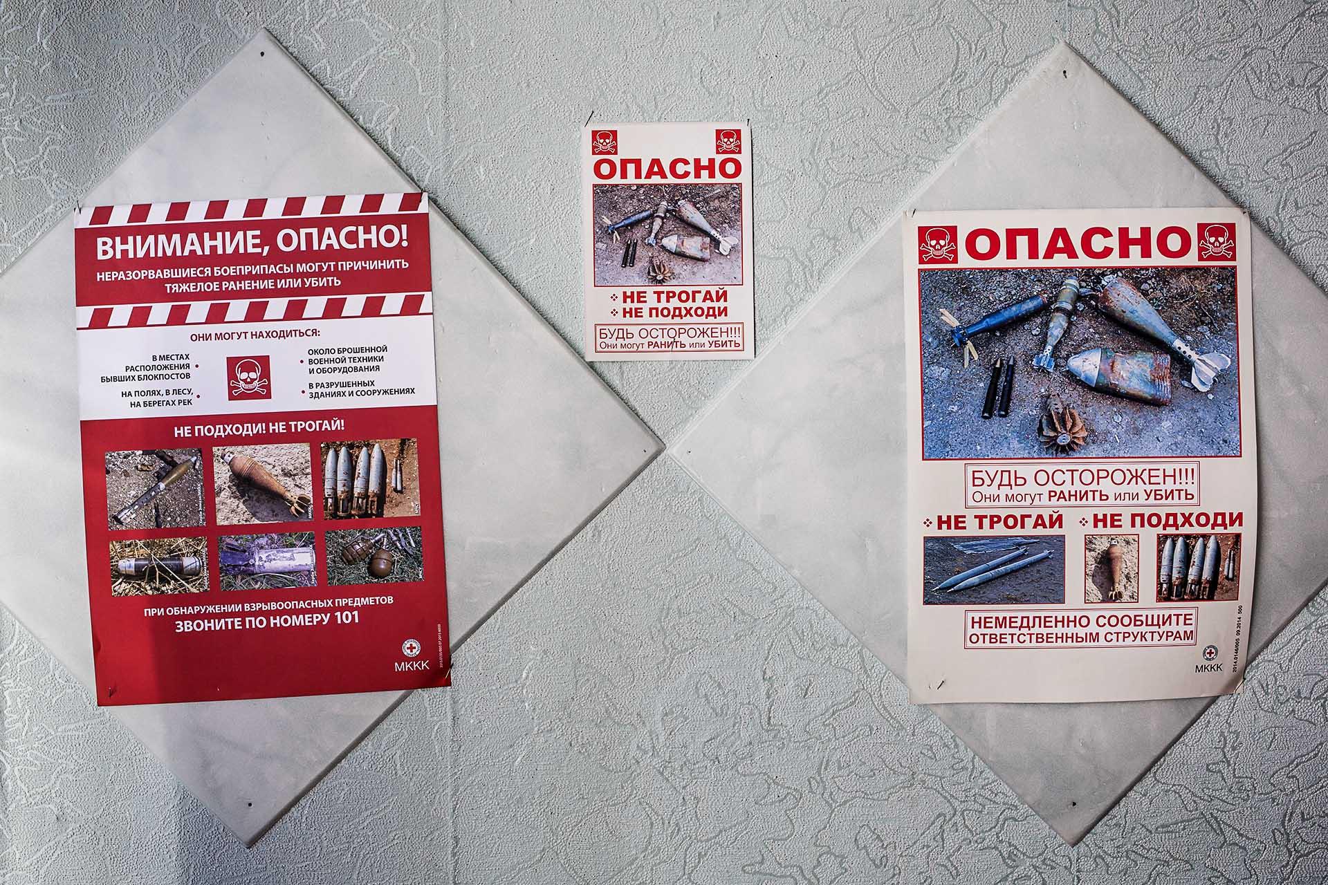 Carteles en un colegio alertando del peligro por artefactos explosivos sin detonar en la zona / (región de Donetsk)