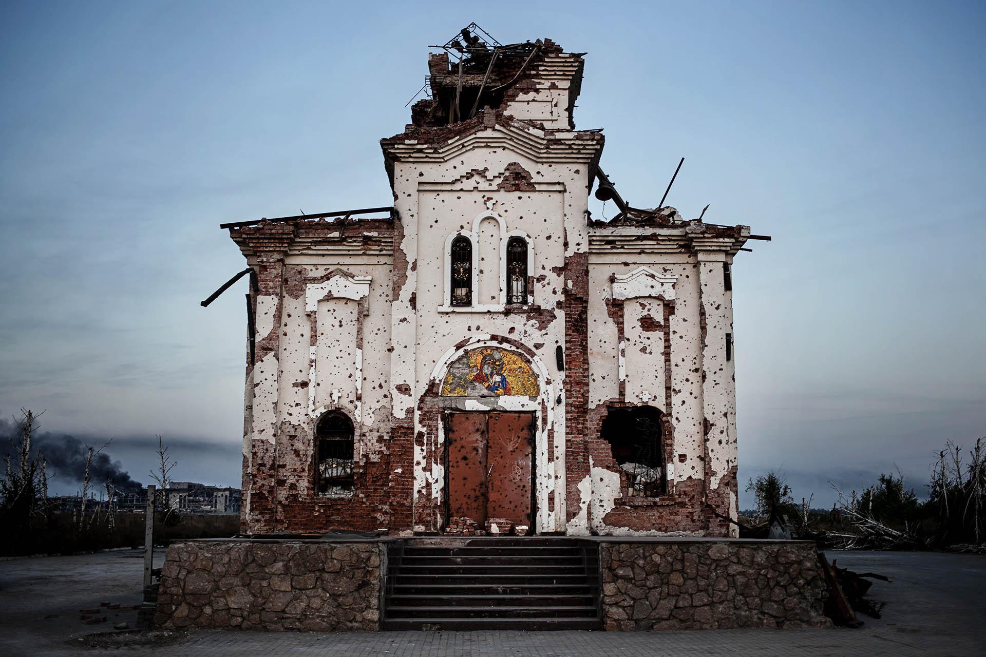 Imagen de una iglesia destrozada por los combates, con el aeropuerto de Donestk al fondo.