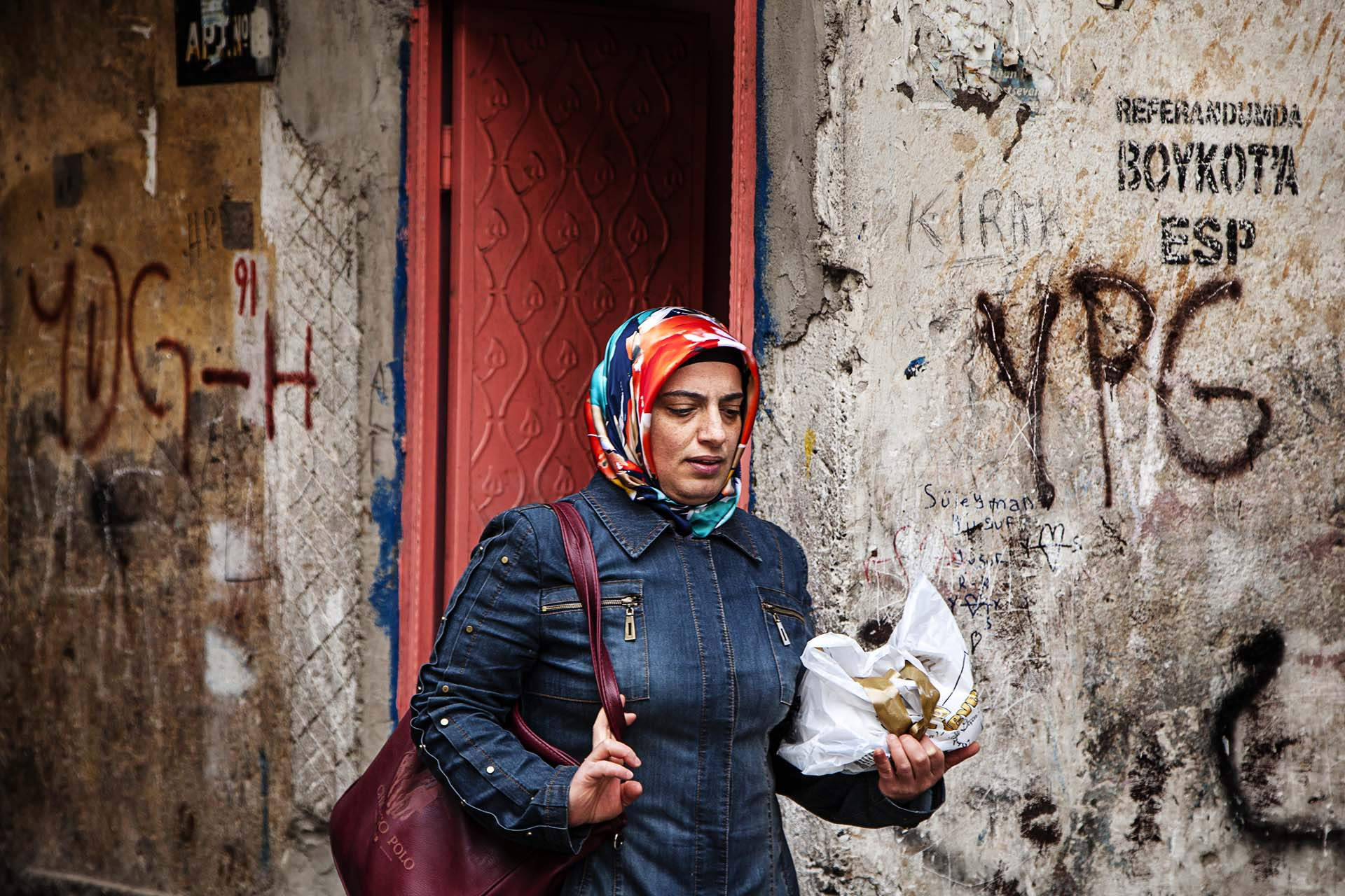 Una mujer pasa ante pintadas a favor de las Unidades de Protección Popular (aparato militar del PKK) y el boicot al referéndum.