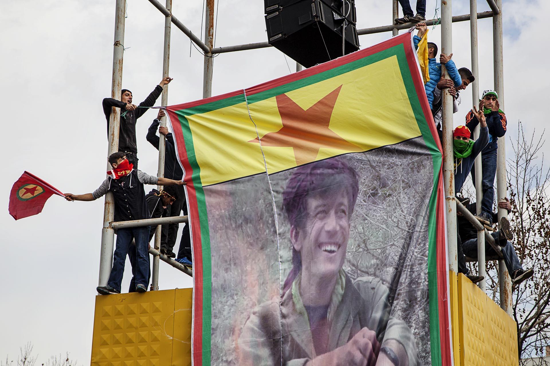 Jóvenes kurdos despliegan una pancarta de un mártir del PKK.