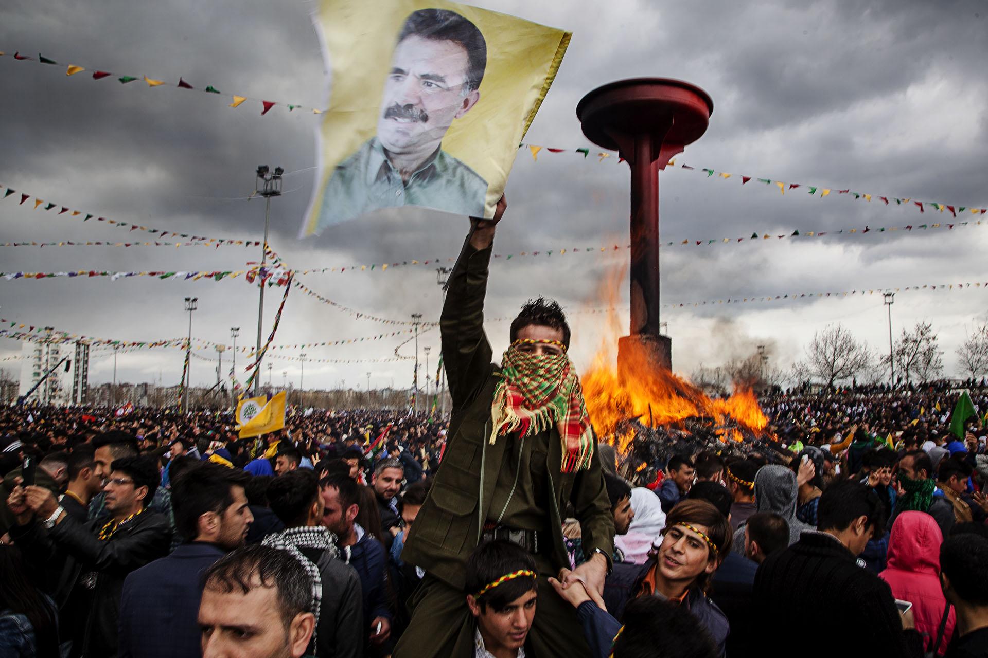 Un joven sostiene una bandera con el rostro de Abdullah Öcallan, líder del PKK, en prisión desde 1.999.