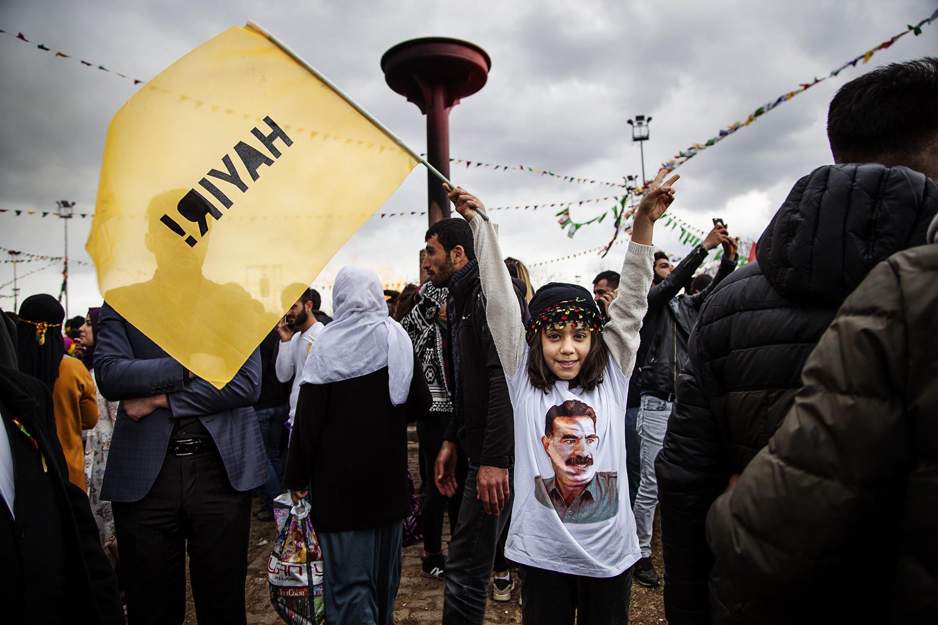 Una niña con una bandera por el NO en el referéndum y una camiseta de Öcallan durante el Newroz.