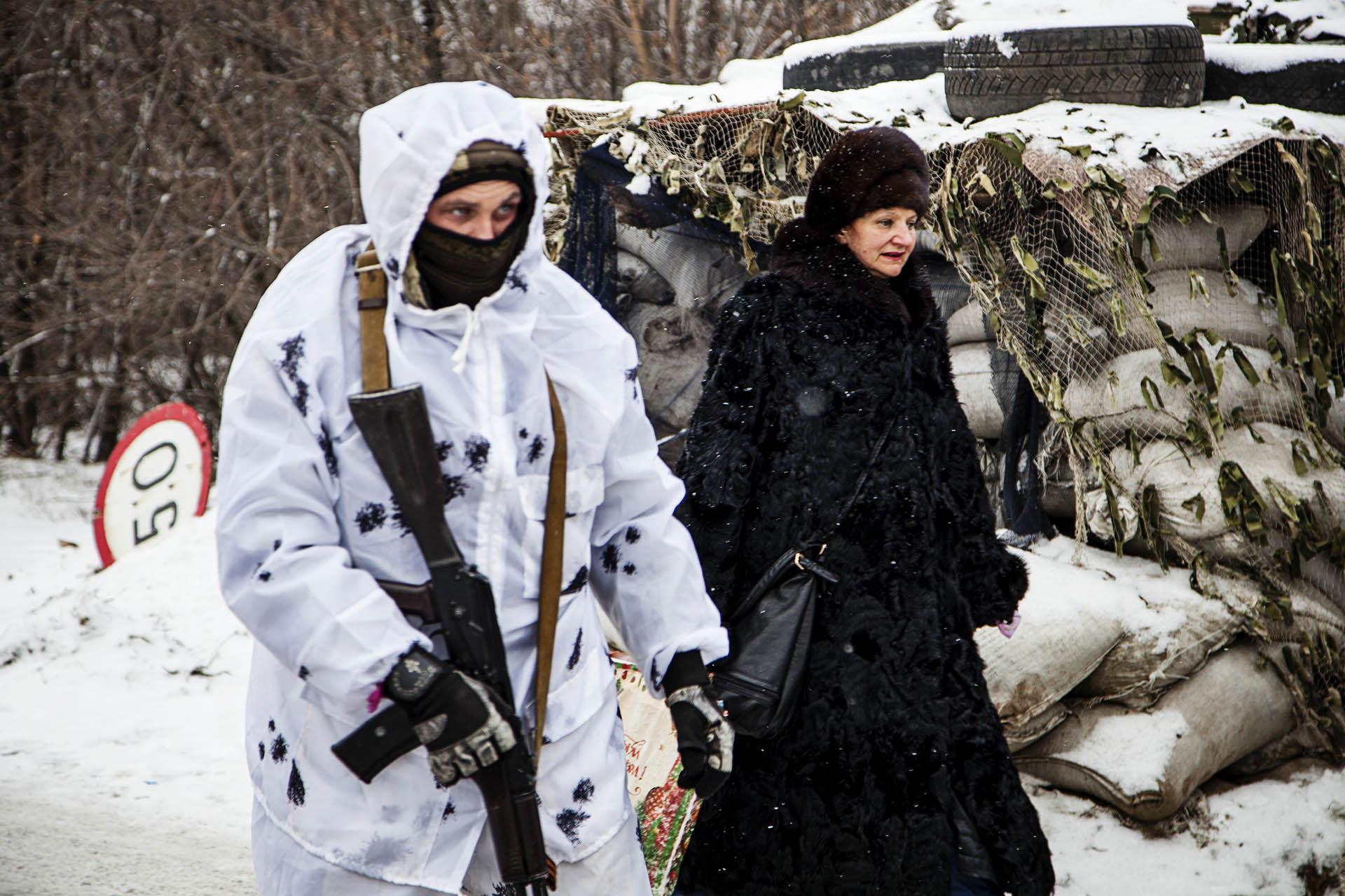 Una mujer cruzando un checkpoint militar.