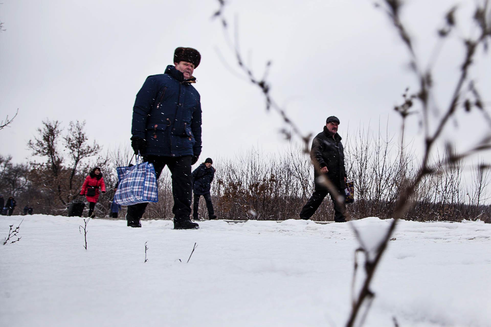 Civiles cruzando la línea de frente hacia territorio rebelde.