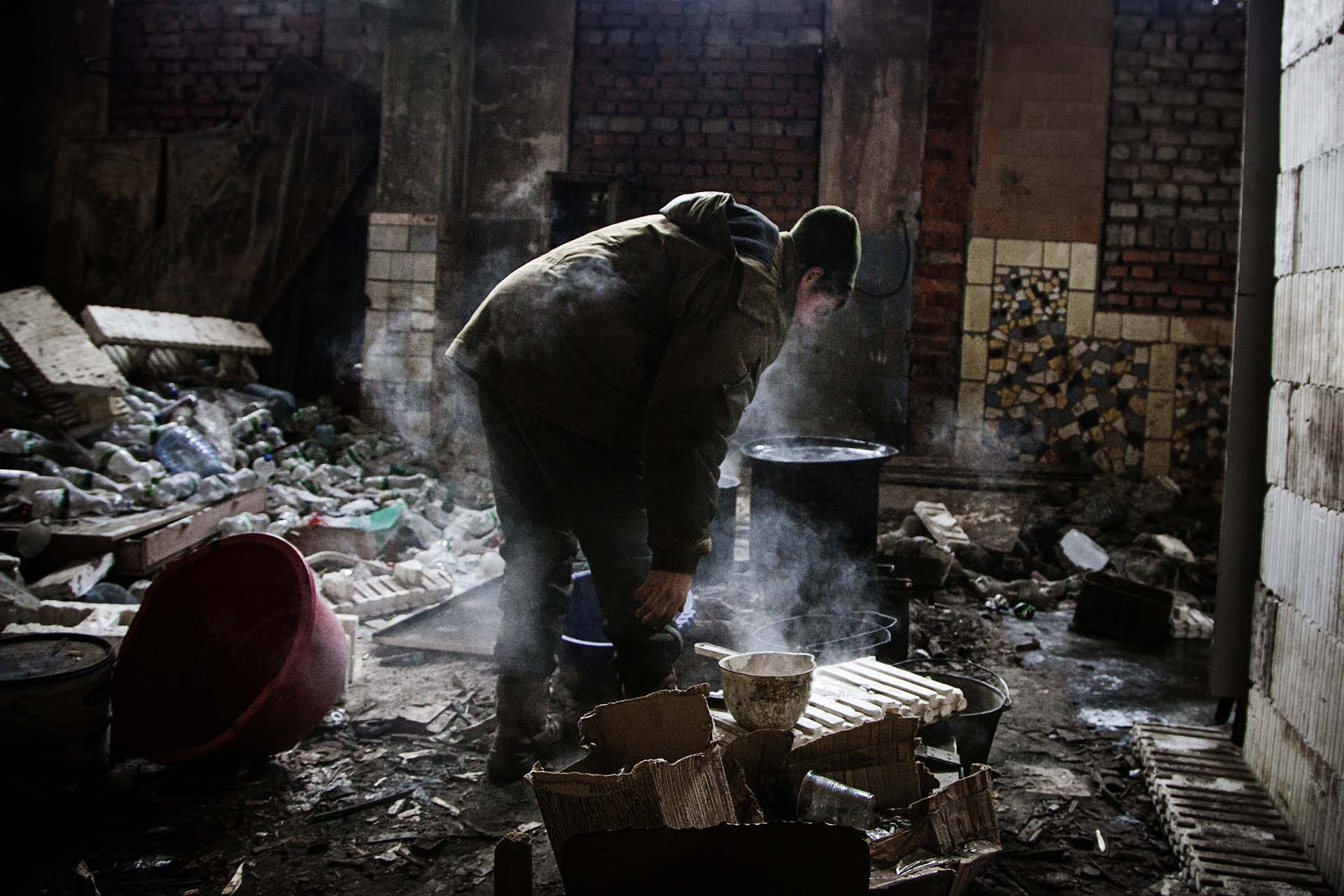 Un soldado ucraniano calienta agua para lavarse en la posición que defienden en primera línea del frente.