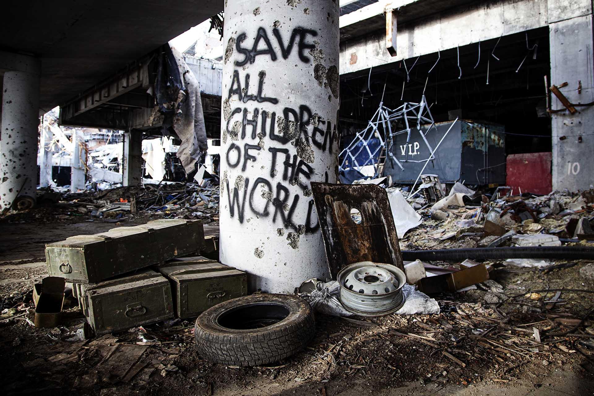 """""""Salvar a todos los niños del mundo"""". Pintada de las tropas de la RPD en un párking del aeropuerto de Donetsk."""