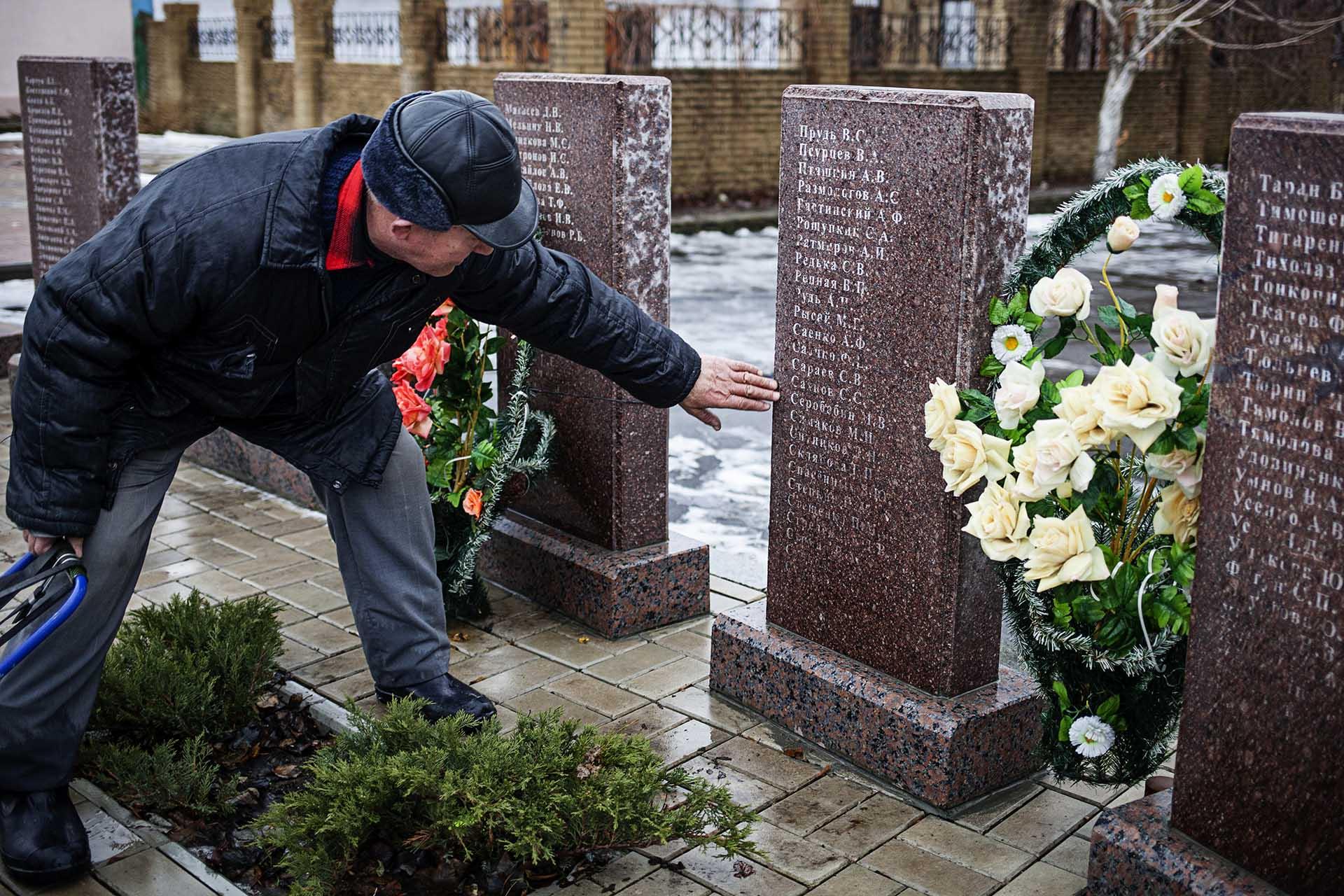 Un hombre señala el nombre de su hijo, muerto por bombardeos ucranianos, en una placa conmemorativa a las afueras de Donetsk.