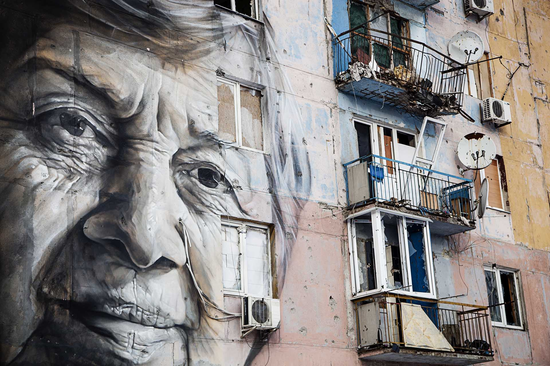 Un edificio alcanzado en varias ocasiones por artillería y fuego cruzado, con un mural en memoria de una profesora asesinada.